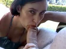 Yummy brunette sensually sucking cock outdoors