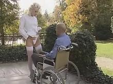 Nurse in white stockings satisfies invalid outdoor