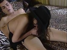 Brunette in black hat does BJ on dappled bedspread