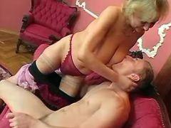 Granny seduces cute guy on red sofa